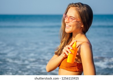 Woman in a stylish coral orange bikini swimsuit applying sun protection on tanned arms and shoulders holding a bottle of spray spf solar block against the blue sea on the shores of the Indian Ocean