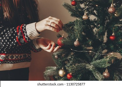 woman in stylish sweater decorating christmas tree in room. merry christmas and happy new year concept. space for text. woman putting on red ornaments. family cozy moments