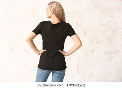 Woman in stylish t-shirt on light background