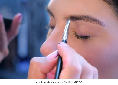 Woman stylist makeup artist making eyebrow shape form for girl, face closeup. Young woman fashion model beauty salon. Applying paint using brush. Glamour stylish fashion industry. Visagiste working.