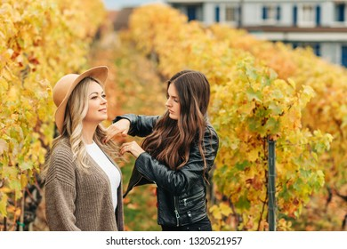 Woman stylist preparing beautiful woman model for photo session, fixing hair