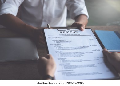 Woman submits job application, Interviewer reading a resume.