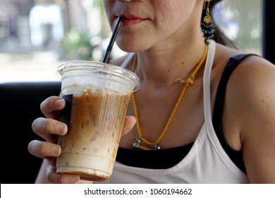 Woman sucks ice coffee with milk, contains in a plastic glass  by straw in coffee shop