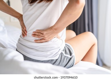Woman suffering from back ache on the bed, healthcare and problem concept - Shutterstock ID 1937094610