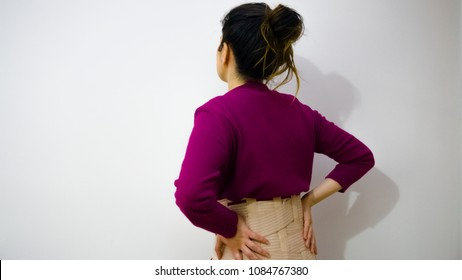 Woman suffering backache on the white background. Young woman with back pain. Lumbago. Back pain or backache concept. Woman with girdle or corset suffering backache or back pain. Copy space.