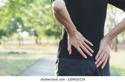 A woman suffering from backache, spinal injury and muscle issue problem at outdoor.