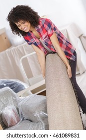 woman suffering from backache while moving carpet