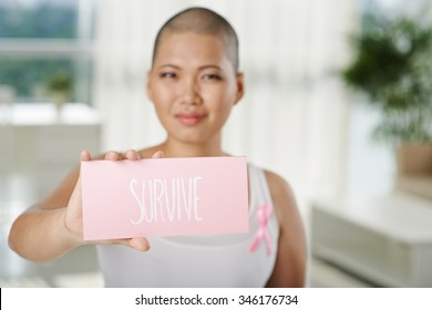 Woman suffering from breast cancer showing plate with survive inscription