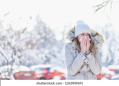 Woman suffering a cold winter outdoors with a snowy mountain in the background. Illness in winter is very popular. Girl with allergy symptom blowing nose. Teen girl using a tissue in a winter park.