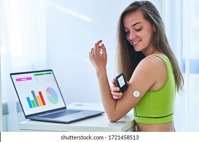 Woman suffering from diabetes using remote sensor and computer for control, monitoring and examining glucose blood levels diagrams and graphs. Diabetics lifestyle and healthcare