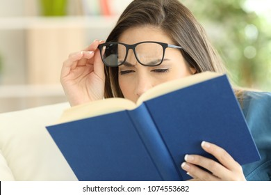 Woman suffering eyestrain trying to read a book at home