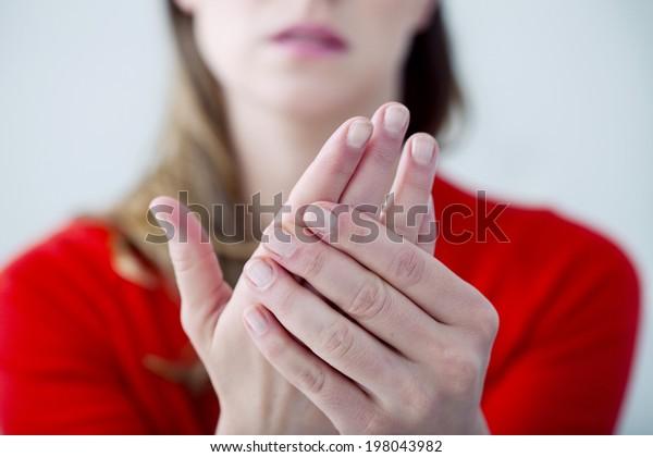 手の痛みに苦しむ女性。