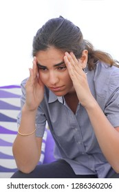 Woman suffering from headache migraine pain at home. Health problem, stress and depression. Female holds head with hand. Concept of health.