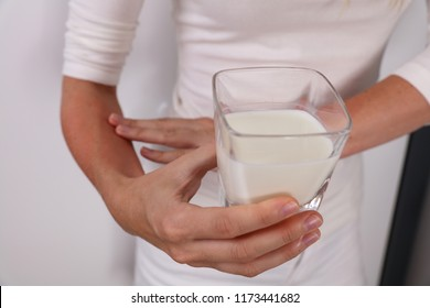 Woman suffering from lactose intolerance holding a galss of milk. Food allergy symptoms rush, itching, skin redness.