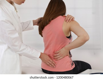 Woman suffering from low back during medical exam. Chiropractic, osteopathy, Physiotherapy. Alternative medicine, pain relief concept.