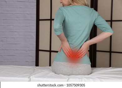 Woman suffering from low back pain. Incorrect sitting posture problems, Muscle spasm, rheumatism. Pain relief, chiropractic concept.