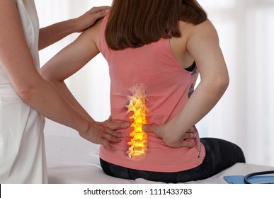 Woman suffering from low back  pain during medical exam. Chiropractic, osteopathy, Physiotherapy. Alternative medicine, pain relief concept.