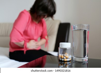 Woman suffering from pain in abdomen. Bottle of pills and water glass on a table, girl sitting on bed clutching her belly, concept of indigestion, stomach ache, menstruation