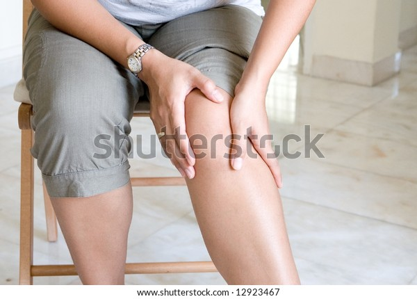 Woman suffering from pain in knee joint.