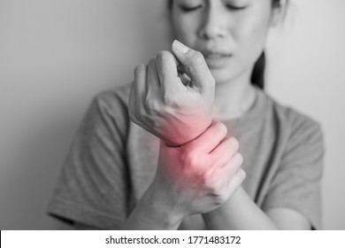 Woman suffering from pain in wrist. Pain in a women wrist. Young woman holding her painful wrist on wall background.