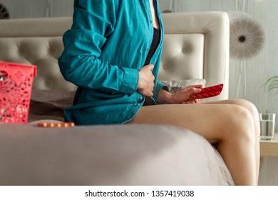 Woman suffering from PMS and critical days. Taking pills, drug, medicine because of stomach ache, abdominal, menstruation pain. Inflammation, infection bladder, cystitis. Treatment and therapy