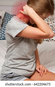Woman suffering shoulder neck ache tired sit on bed