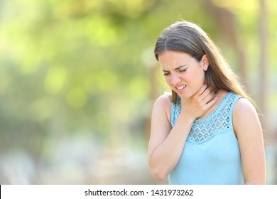 Woman suffering sore throat in a park standing outdoors in a park