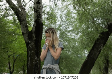 Woman suffering from spring poplar pollen allergy. Sneezing into handkerchief