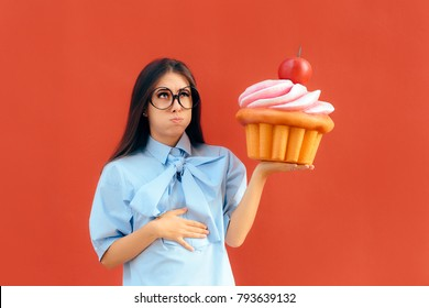Woman Suffering Stomach Ache After Eating Too Much Cupcake. Hungry overeating girl binge eating indulging on sweets