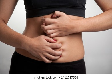 Woman suffering from stomach pain, isolated in grey