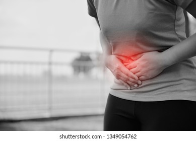A woman is suffering stomach pain from running or workout, pain and colic is a frequent problem while running or workout.