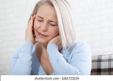 Woman suffering from stress or a headache grimacing in pain as she holds the back of her neck with her other hand to her temple, with copyspace. Concept photo with indicating location of the pain.