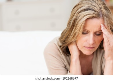 Woman suffering from stress or a headache grimacing in pain as she holds the back of her neck with her other hand to her temple, with copyspace