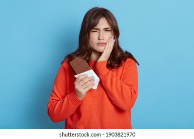 Woman suffering from toothache after eating chocolate, frowning her face, covering cheek with palm, female with dark hair wearing orange casual sweater.