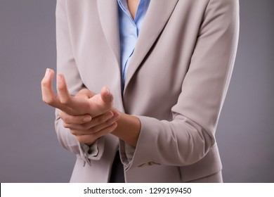 woman suffering from trigger finger, cps, wrist joint pain, arthritis, gout; joint care in clinic or hospital, health, medical concept; tan skin asian woman model