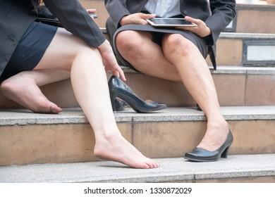 Woman is suffering from wear black high heel shoes