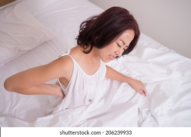 woman suffers from back pain on bedroom, concept of office syndrome, spinal or lower back problem