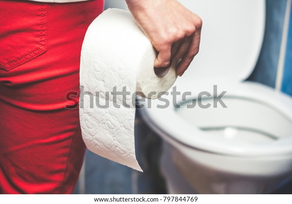 Woman suffers from diarrhea holds toilet paper roll in front of toilet bowl. Stomach upset.