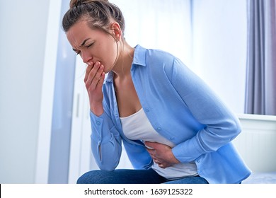 Woman suffers from nausea and vomiting during gastrointestinal system disease or food poisoning, health problems