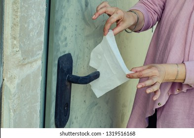 A woman suffers from obsessive-compulsive disorder (OCD) in form of monophobia covers the door handle with hygiene napkin.