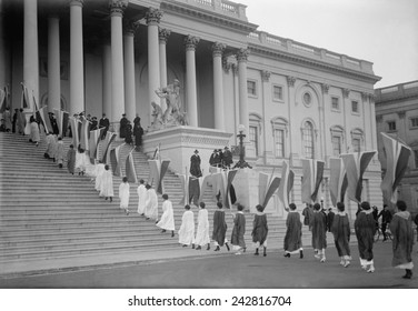 Woman Suffrage demonstration with banners at the U.S. Capitol in 1917. View of Procession ascending Capitol steps.