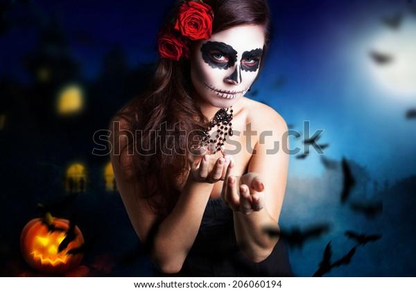 femme avec un crâne à sucre en stylo devant un fond d'halloween