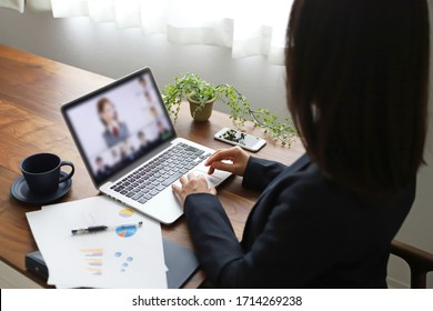 A woman in a suit doing telework at home