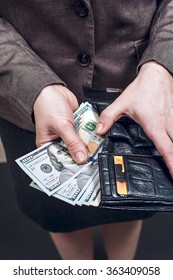 Woman in suit with leather wallet full of US dollars. Conception of safe storage and protection of cash. Financial theme.