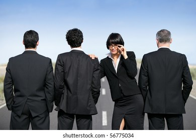 Woman in suit standing near men in suit
