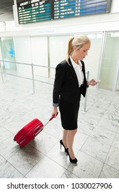 woman with suitcase and mobile phone at the airport