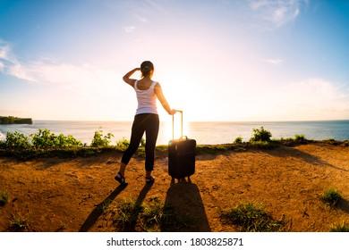 空と地面にスーツケースを持つ女性
