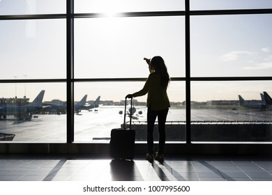 Woman with suitcase standing in airport