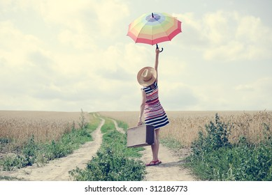 Woman with suitcase standing on road between field of wheat. Backview of girl in hat rising umbrella.