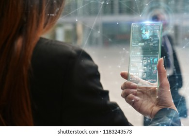 A woman in suits, uses a futuristic glass phone with the latest advanced holographic technology. Concept of: future, technology, smartphone, augmented reality